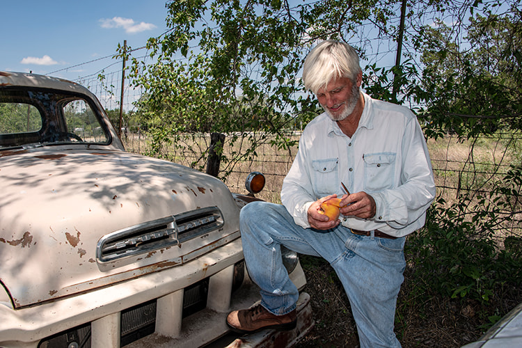 Russ Studebaker props against a truck and cuts into a peach.