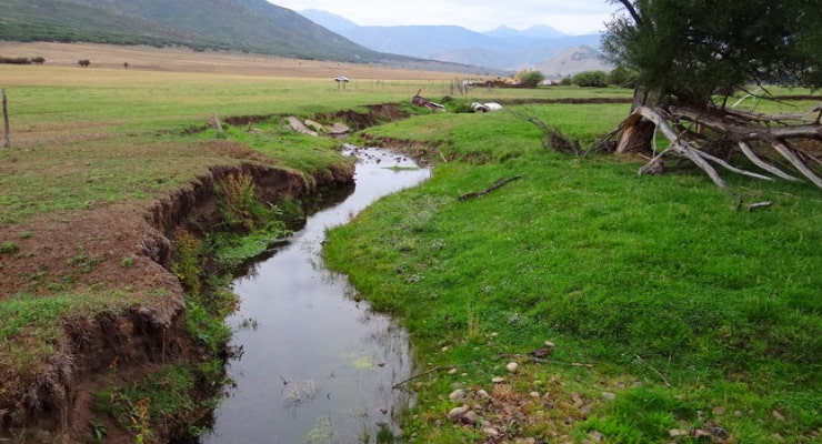 """Evidence of channel erosion is shown alongside the banks of a stream"""