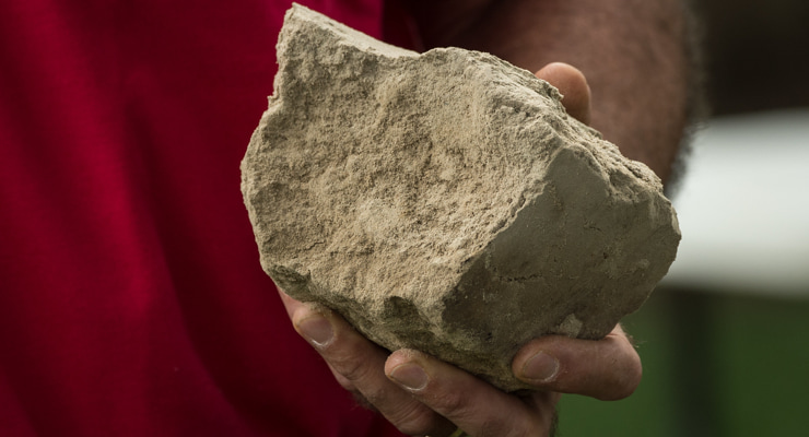 """Photo of someone holding a large chunk of dry, compacted soil"""