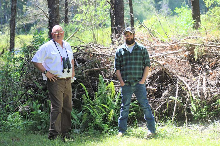 Mark stands with Frank Curtin, NRCS Soil Conservationist, with wetland habitat in the background.