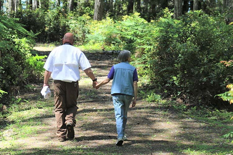 Mark and Beth Bister walking while holding hands to view the wildlife on their farm.