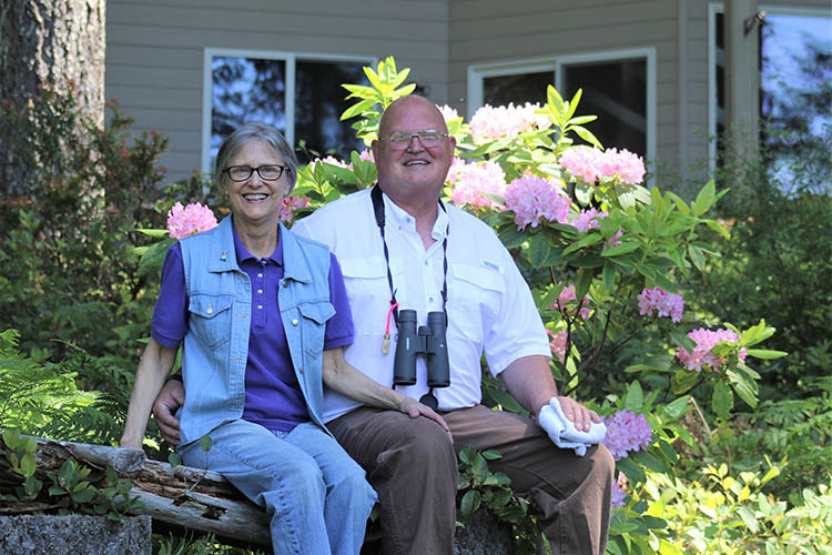 Mark and Beth Biser sit on a log bench, owners of Still Waters Farm in Mason County, Washington, sit on a bench in front of their farm.