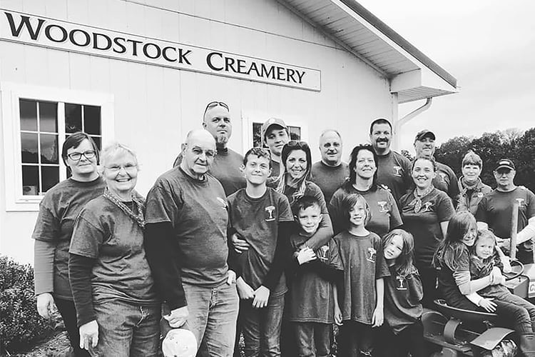 Family photo of the Young family standing in front of the Woodstock Creamery Farm Store at Valleyside Farm.