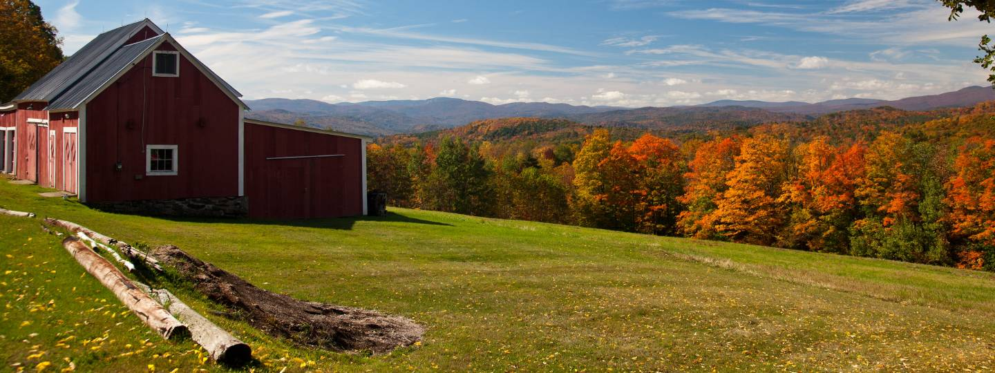 Barn on grass field with fall foliage