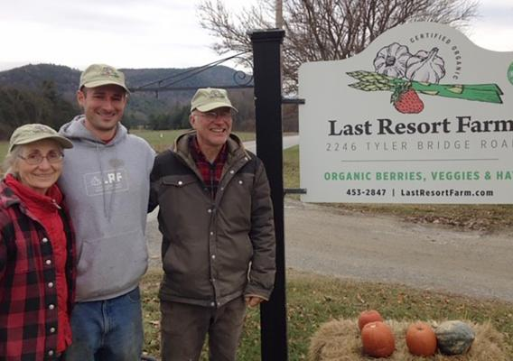 Eugenie Doyle (left) and Sam Burr (right) with their son Silas (center) beside their Last Resort Farm sign
