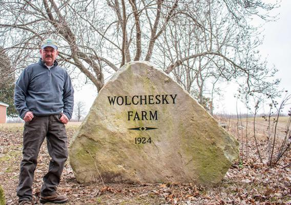 John Wolchesky, Jr. standing in front of his family rock for Wolchesky Farm.