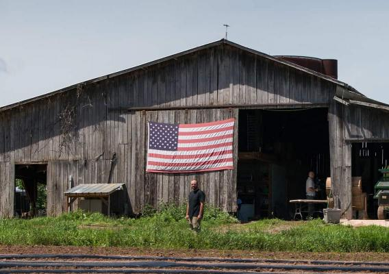 Veteran farmer standing in front of barn with an American flag behind him