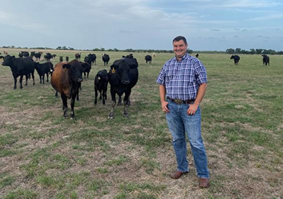 Scott Reed dressed in blue jeans and a blue plaid shirt stands in a pasture with cows in the background.
