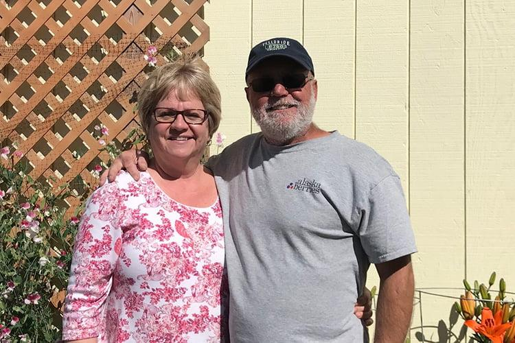 Alaskan farmers Brian and Laurie Olson stand together.