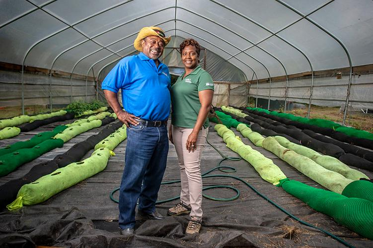 A farmer and NRCS District Conservationist stand in a high tunnel.