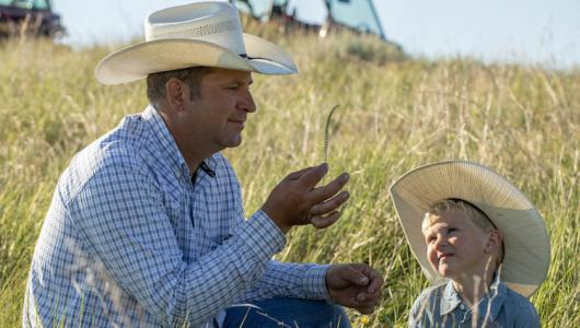 Britton Blair teaches his son Jack how to identify different grass species on their South Dakota ranch